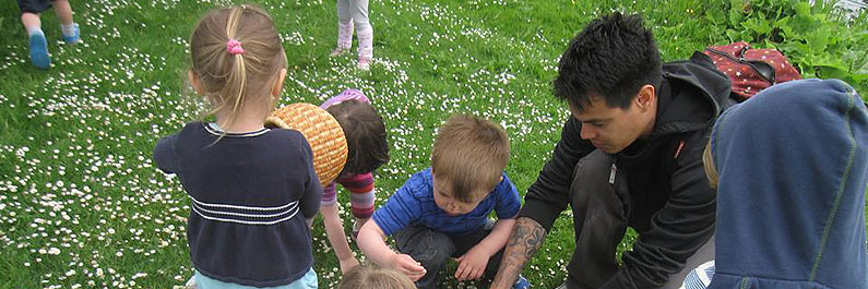 Teacher helps Preschool Students Pick Flowers