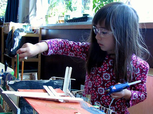 Preschool student crafts an art project with a glue gun