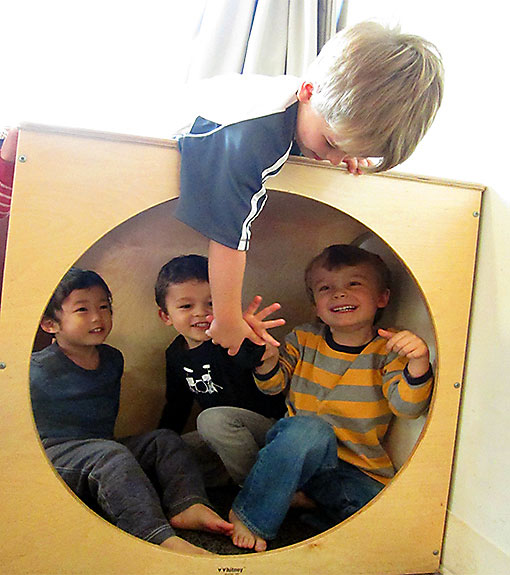 Preschool Students Play in a Wooden Box