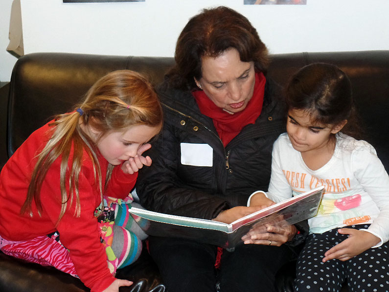 A Parent Reads to Two Students