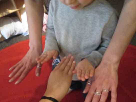 Preschool student compares hands with a teacher and a parent