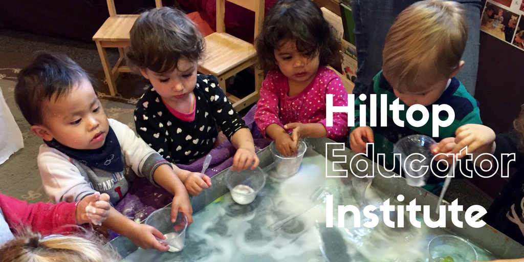 Children Playing Around A Desk. One of many banner photos used to promote the Hilltop Educator Institute