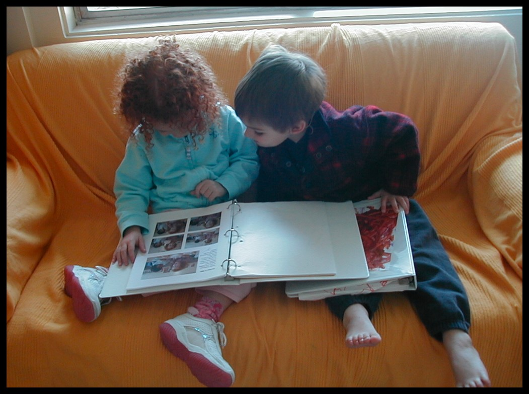 Two children, Milo and Grace, reading their class journal on the couch. Example of learning story.