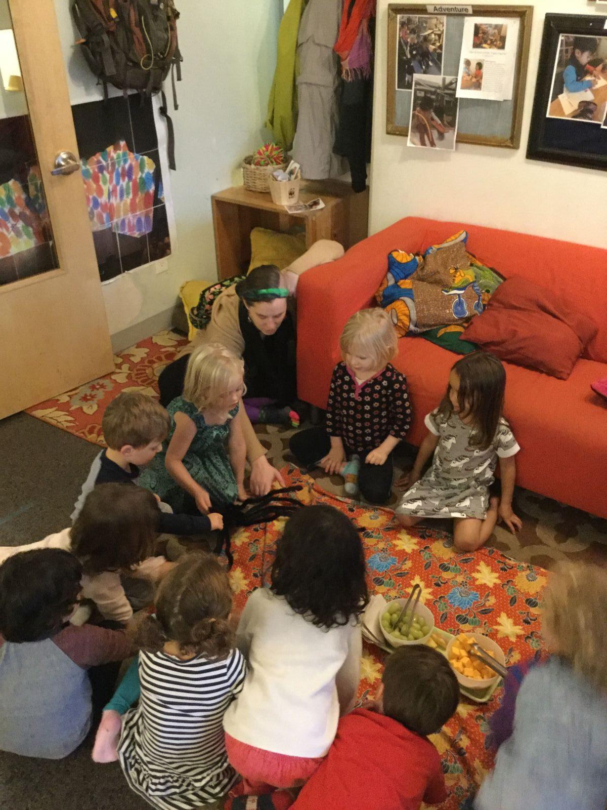 Children watching an electronic spider crawl